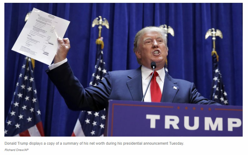Donald Trump displays a copy of a summary of his net worth during his presidential announcement Tuesday