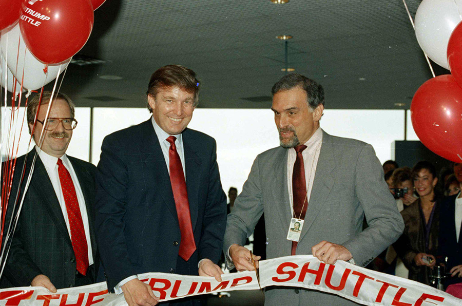 Donald Trump holds a ribbon at Logan International Airport in Boston, as Massport deputy-executive director Patrick Moscaritolo cuts it to officially open the Trump Shuttle airline terminal on June 8, 1989
